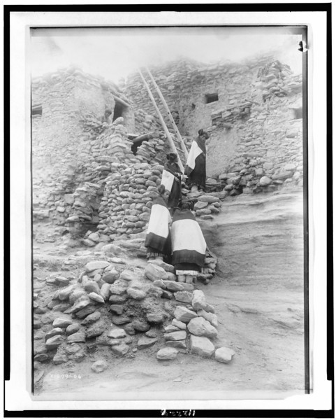 Description of  Title: Cliff perched homes--Hopi.  <br />Date Created/Published: c1906.  <br />Summary: Four Hopi women in front of pueblo buildings.  <br />Photograph by Edward S. Curtis, Curtis (Edward S.) Collection, Library of Congress Prints and Photographs Division Washington, D.C.