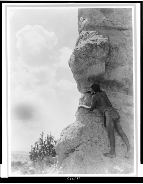 Description of  Title: The sentinel--San Ildefonso.  <br />Date Created/Published: c1927.  <br />Summary: San Ildefonso man peering from behind large rock formation.  <br />Photograph by Edward S. Curtis, Curtis (Edward S.) Collection, Library of Congress Prints and Photographs Division Washington, D.C.