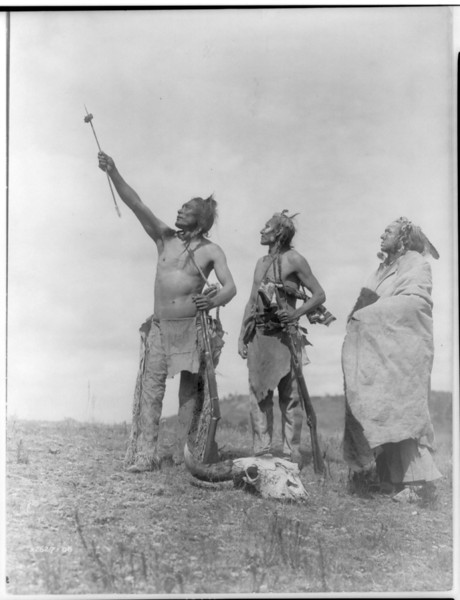 Description of  Title: The Oath--Apsaroke.  <br />Date Created/Published: c1908 November 19.  <br />Summary: Three Apsaroke men gazing skyward, two holding rifles, one with object skewered on arrow pointed skyward, bison skull at their feet.  <br />Photograph by Edward S. Curtis, Curtis (Edward S.) Collection, Library of Congress Prints and Photographs Division Washington, D.C.