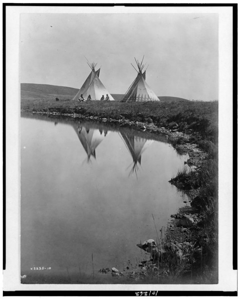 Description of  Title: At the water's edge--Piegan.  <br />Date Created/Published: 1910, c1910.  <br />Summary: Two tepees reflected in water of pond, with four Piegan Indians seated in front of one tepee.  <br />Photograph by Edward S. Curtis, Curtis (Edward S.) Collection, Library of Congress Prints and Photographs Division Washington, D.C.