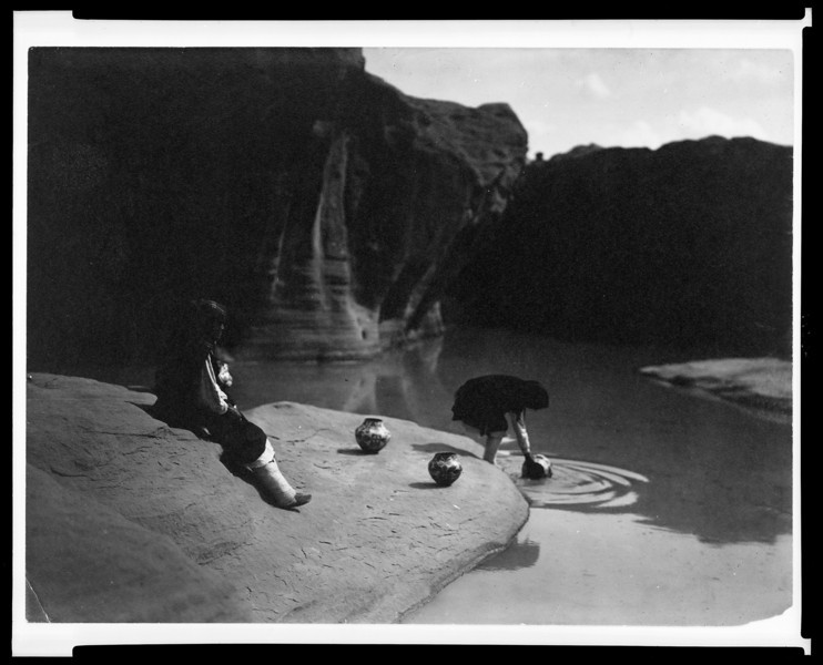 Description of  Title: At the old well of Acoma  <br />Date Created/Published: c1904 November 12.  <br />Summary: Acoma girl, seated on rock, watches as another girl fills a pottery vessel with water from a pool.  <br />Photograph by Edward S. Curtis, Curtis (Edward S.) Collection, Library of Congress Prints and Photographs Division Washington, D.C.