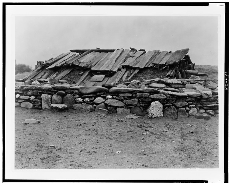 Description of  Title: Hupa sweat-house.  <br />Date Created/Published: 1923.  <br />Summary: Underground building covered with wood plank roof, surrounded by wall of large rocks.  <br />Photograph by Edward S. Curtis, Curtis (Edward S.) Collection, Library of Congress Prints and Photographs Division Washington, D.C.