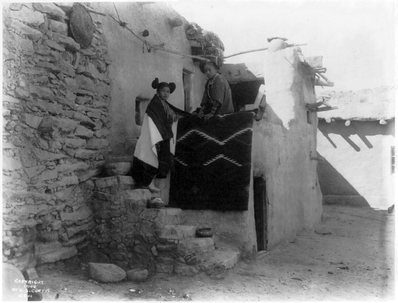 Description of  Title: Tewa girls.  <br />Date Created/Published: c1900.  <br />Summary: Two Tewa girls standing outside pueblo building.  <br />Photograph by Edward S. Curtis, Curtis (Edward S.) Collection, Library of Congress Prints and Photographs Division Washington, D.C.