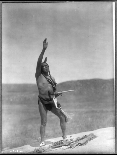 Description of  Title: Invocation--Sioux.  <br />Date Created/Published: c1907 December 26.  <br />Summary: Dakota man, wearing breechcloth, holding pipe, with right hand raised skyward.  <br />Photograph by Edward S. Curtis, Curtis (Edward S.) Collection, Library of Congress Prints and Photographs Division Washington, D.C.