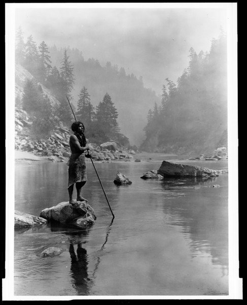 Description of  Title: A smoky day at the Sugar Bowl--Hupa.  <br />Date Created/Published: c1923 June 30.  <br />Summary: Hupa man with spear, standing on rock midstream, in background, fog partially obscures trees on mountainsides.  <br />Photograph by Edward S. Curtis, Curtis (Edward S.) Collection, Library of Congress Prints and Photographs Division Washington, D.C.