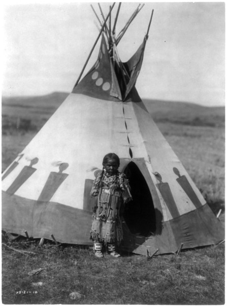 Description of  Title: A child's lodge.  <br />Date Created/Published: c1910 December 10.  <br />Summary: Piegan girl standing outside small tipi.  <br />Photograph by Edward S. Curtis, Curtis (Edward S.) Collection, Library of Congress Prints and Photographs Division Washington, D.C.