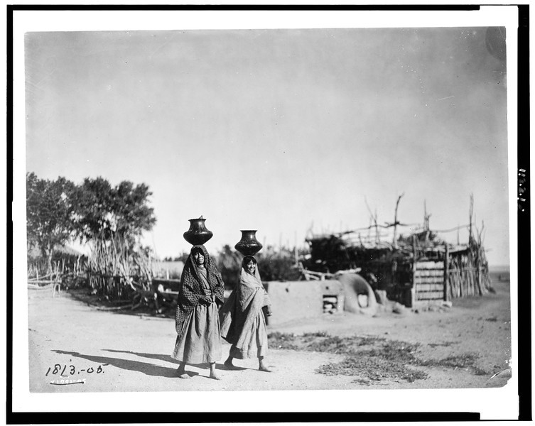 Description of  Title: In the village of Santa Clara.  <br />Date Created/Published: c1905.  <br />Summary: Two Pueblo women carrying jugs on their heads; trees, rail fence, stick structure along dirt path in the background.  <br />Photograph by Edward S. Curtis, Curtis (Edward S.) Collection, Library of Congress Prints and Photographs Division Washington, D.C.