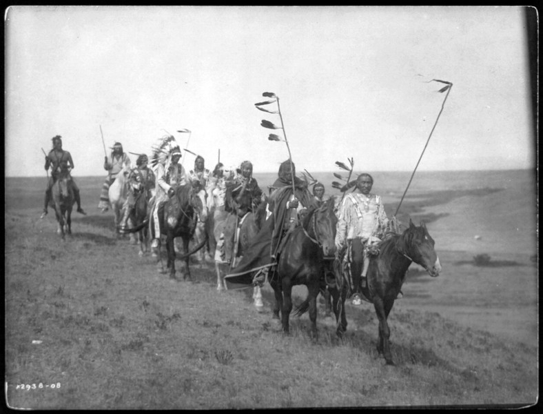 Description of  Title: On the war path--Atsina.  <br />Date Created/Published: c1908 November 19.  <br />Summary: Small band of Atsina men on horseback, some carrying staffs with feathers, one wearing a war bonnet.  <br />Photograph by Edward S. Curtis, Curtis (Edward S.) Collection, Library of Congress Prints and Photographs Division Washington, D.C.