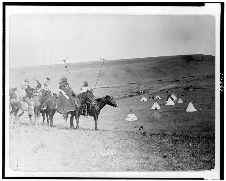 Description of  Title: War party's farewell--Atsina.  <br />Date Created/Published: 1908.  <br />Summary: Four Atsina Indians on horseback overlooking tepees in valley beyond.  <br />Photograph by Edward S. Curtis, Curtis (Edward S.) Collection, Library of Congress Prints and Photographs Division Washington, D.C.