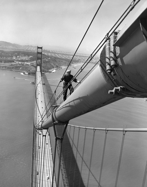 Description of  Bill Gaure, maintenance worker on the Golden Gate Bridge in San Francisco, nears the top of the north tower after nearly a half-mile uphill hike from the center of the span, May 15, 1952. In the background, at center, is a residential area of San Francisco, and at upper left is part of the Presidio. The bridge was built right where the Pacific Ocean and San Francisco Bay meet. (AP Photo/Ernest K. Bennett)