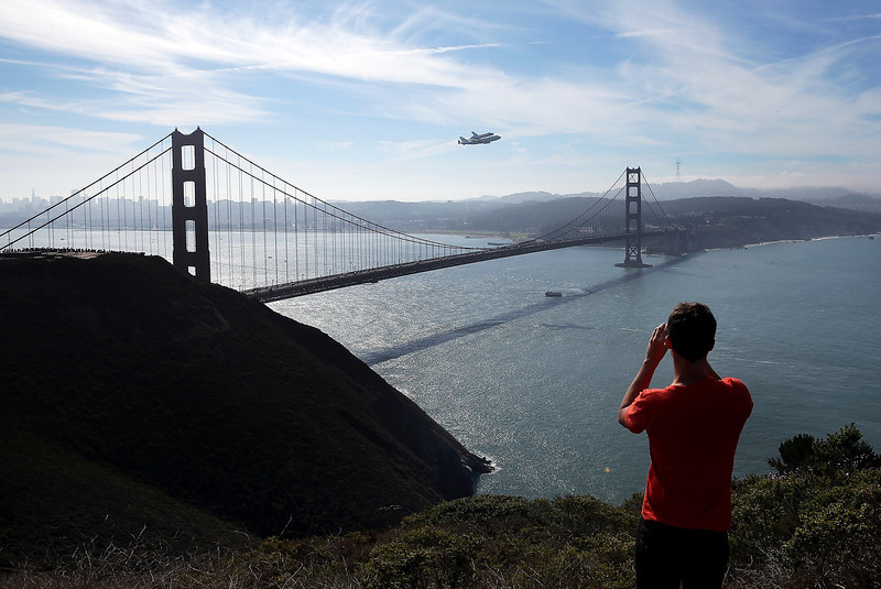 Description of  A spectator takes a photo of the Space Shuttle Endeavor as it flies on top of a modified 747 jumbo jet over the Golden Gate Bridge while traveling to Los Angeles on September 21, 2012 in Sausalito, California. The Space Shuttle Endeavor did a 4-1/2 hour tour over California landmarks before heading to Los Angeles International Airport where it would be prepared to be moved to its new permanent home at the California Science Center in downtown Los Angeles. (Photo by Justin Sullivan/Getty Images)