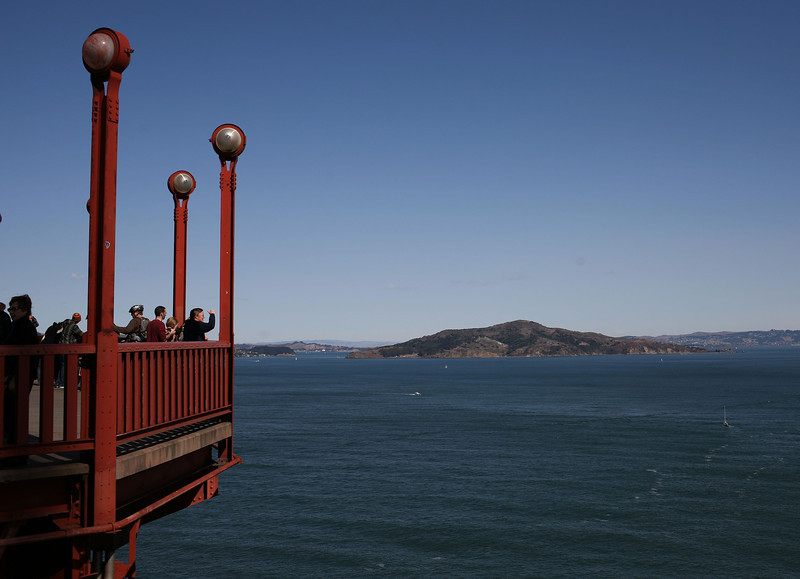 Description of  Tourists take photos from a vantage point on the span of the Golden Gate Bridge October 10, 2008 in San Francisco, California. (Photo by Justin Sullivan/Getty Images)