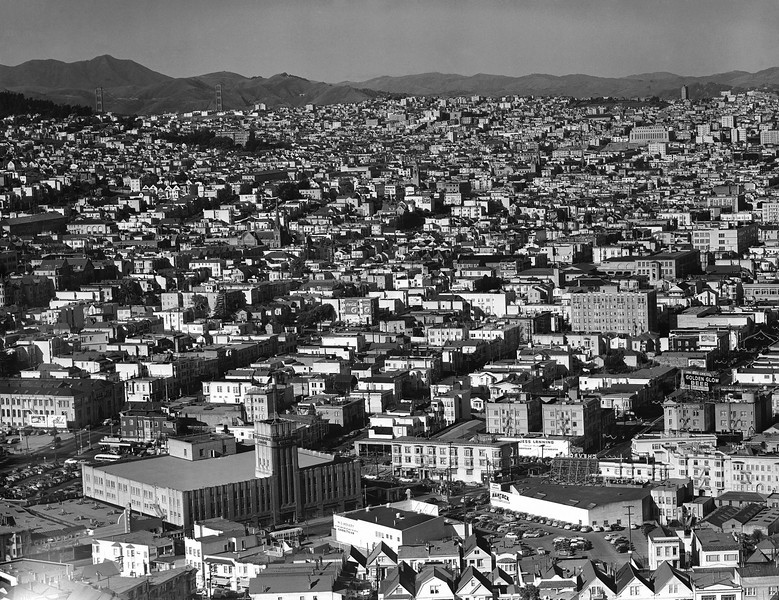 Description of  General viewed of the over-crowded Mission district of San Francisco April 27, 1950. (Mission Street runs diagonally across the foreground from lower left to right center.) The building with a long row of vertical windows at upper right is the U.S. Mint, and upper left are the towers of the Golden Gate bridge. The highest point of Mt. Tamalpias across the Golden Gate in Marin County is just above the left tower. (AP Photo/EK Bennett)