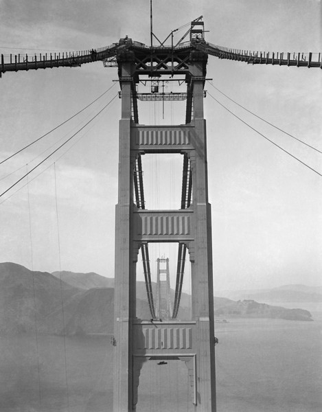 Description of  Preparations for spinning the cables of the Golden Gate Bridge between Marin Country and San Francisco occupied crews October 10, 1935. They were busy erecting storm cable system, telephone system and various units of the spinning equipment for the $35,000,000 structure. The cable, stretching from the tower in the foreground to the Marin Country or North side, will be 36 1/2 inches in diameter. The Catwalks with some of the storm cables is shown. (AP Photo)