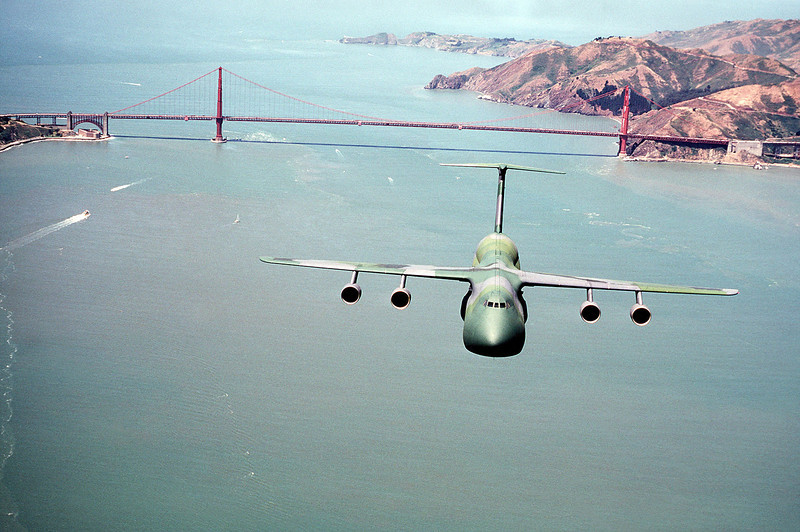 Description of  An air-to-air front view of a C-5A Galaxy aircraft, in a camouflage paint scheme, as it flies over the San Francisco Bay. The Golden Gate Bridge can be seen in the background. (Photo by USAF, Getty Images)