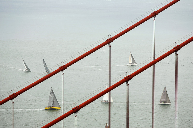 Description of  Boats sail past the Golden Gate Bridge during the Spinnaker Cup on May 22, 2009 in San Francisco, California. The Spinnaker Cup, which is one of six regattas in the San Francisco 2009 IRC Championship Series, is a distance race that starts in San Francisco and finishes in Monterey, California. (Photo by Ezra Shaw/Getty Images)
