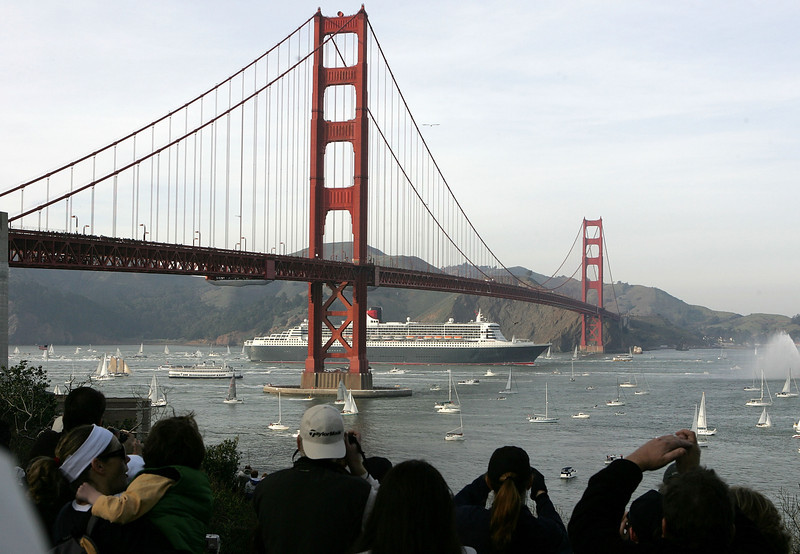 Description of  People line up to see Cunard's Queen Mary 2, the largest ocean liner in the world, as it sails under the Golden Gate Bridge into the San Francisco Bay February 4, 2007 in San Francisco, California. The Queen Mary 2 made her maiden port call after sailing under the Golden Gate Bridge. The ship would dock in San Francisco overnight before continuing on her first world cruise.  (Photo by Justin Sullivan/Getty Images)