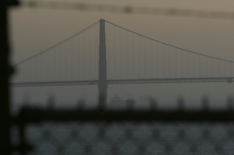 Description of  The Golden Gate Bridge is visible through the fence and barbed wire surrounding the prison recreation yard as the sun sets on Alcatraz Island, 14 June 2007 in San Francisco Bay of California. (ROBYN BECK/AFP/Getty Images)