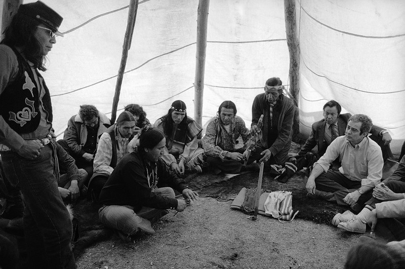 Description of  Assistant U.S. attorney general Kent Frizzell, right, listens to AIM Indian as other AIM leaders sit by in tepee prior to signing of peace settlement, April 5, 1973 in Wounded Knee, South Dakota. Kneeling is Wallace Black Elk and to his left are AIM leaders Russell Means, Dennis Banks and Carter Camp, in that order. (AP Photo/Jim Mone)
