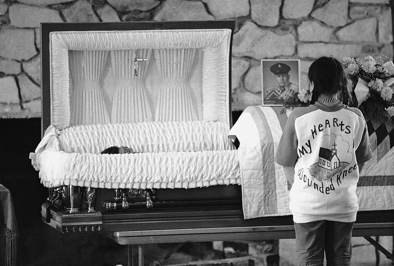 "Description of  A young Indian girl wearing a sweatshirt proclaiming ""My hearts in Wounded Knee,"" stands in front of the casket of Lawrence Lamont during funeral on May 4, 1973 in Wounded Knee. Lamont died last week in Wounded Knee during a shooting confrontation between militant AIM Indians and federal lawman. On the casket is picture of Lamont in his Military Uniform. (AP Photo)"