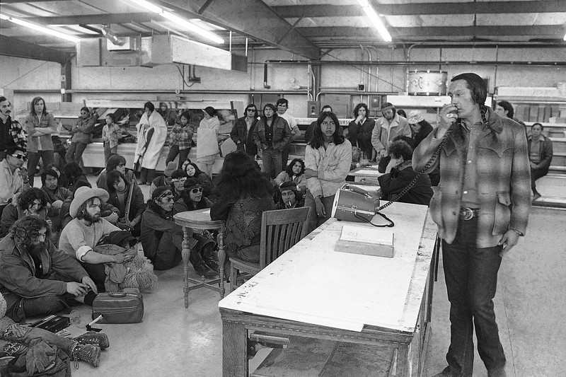 Description of  Russell Means, one of the AIM leaders in Wounded Knee, South Dakota on March 12, 1973, explains to followers what is expected of them now that they are a new sovereign nation. (AP Photo)