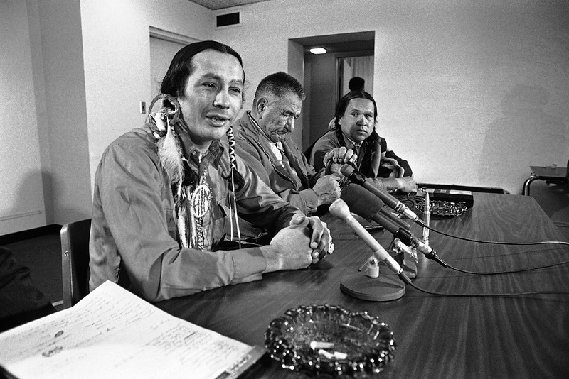 Description of  Russell Means, left, leader of the American Indian Movement, answers questions about the occupation of Wounded Knee, S.D., Sunday, April 9, 1973 at a Washington news conference. Also at the conference are Chief Terronez Bad Cob, center, 2nd Leonard Crow Dog. Means will testify on Monday before the House Indian Affairs subcommittee. (AP Photo/Charles Gorry)