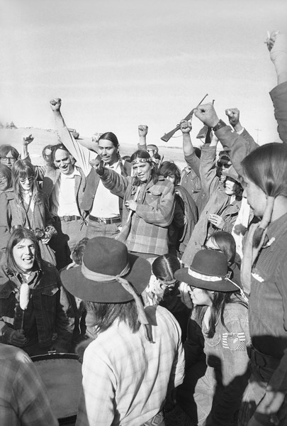 Description of  AIM leader Carter Camp, white shirt, and attorney William Kunstler, to Camp's right, join AIM Indians in celebrating the pullout of federal lawmen from roadblocks in Wounded Knee, South Dakota , March 10, 1973, which have surrounded Wounded Knee for over a week following takeover of the town by AIM Indians. (AP Photo)