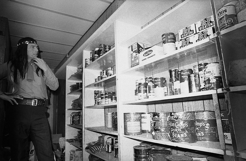 Description of  Dennis Banks, one of leaders of the American Indian Movement, shows depleted food supply at Wounded Knee, South Dakota, March 25, 1973. AIM has controlled the village for almost four weeks. (AP Photo/Fred Jewell)