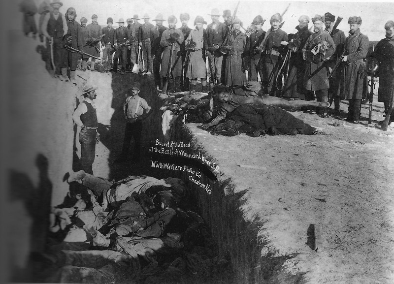 "Description of  ""Burial of the dead at the battle of Wounded Knee, S.D."" U.S. Soldiers putting Indians in common grave; some corpses are frozen in different positions. South Dakota. c1891 Jan. 17. Northwestern Photo Co. (Trager & Kuhn) Chadron, Neb. (Library of Congress Prints and Photographs Division)"