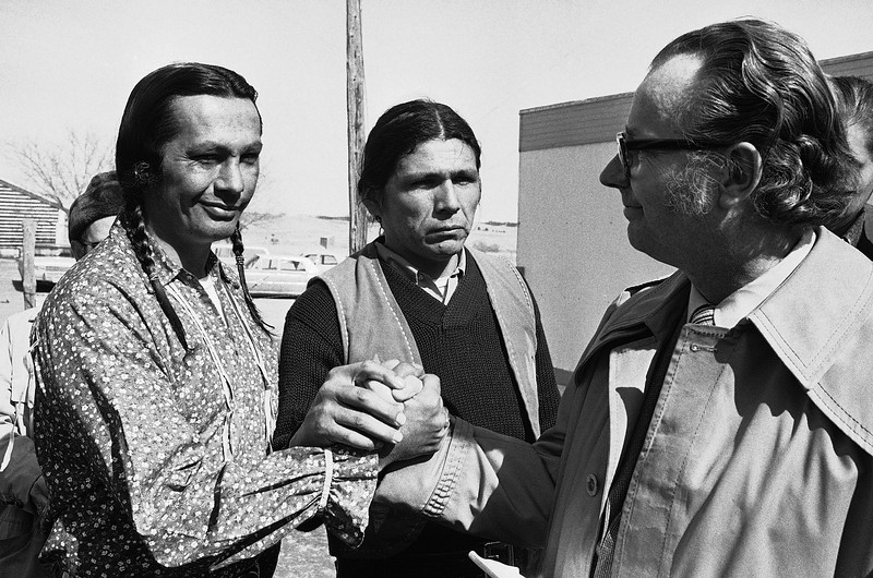 Description of  Russell Means, left, leader of the American Indian Movement (AIM) at Wounded Knee, March 9, 1973, exchanges a handshake with Bishop James Armstrong of the United Methodist Church, right, after Armstrong presented a proposal for further negotiations with the government. Dennis Banks, another AIM leader looks on. (AP Photo)
