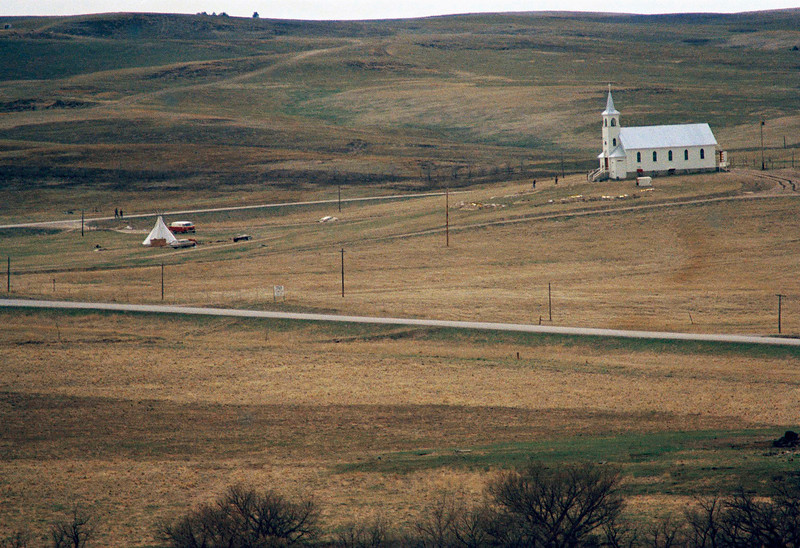 Description of  View  of the church at Wounded Knee, South Dakota on March 27, 1973. In foreground is a make-shift barricade constructed by supporters of AIM during their seizure of the hamlet. (AP Photo)