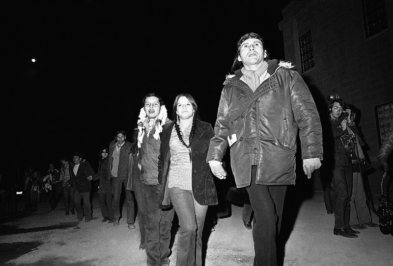 Description of  Dennis Banks, field director of the American Indian Movement takes the lead of an estimated 150 Indians who joined in a march around the parking lot of the county jail, Feb. 12, 1973 in Rapid City, South Dakota, where 40 Indians are held on riot charges. (AP Photo/Jim Mone)