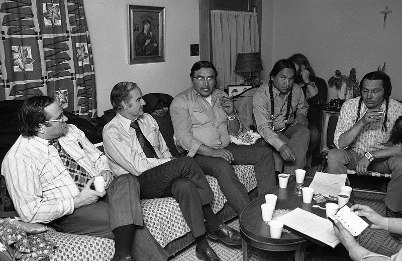 Description of  Sens. James Abourezk, left, and George McGovern listen to Sefert Youngbear, center, during negotiations, Thursday, March 2, 1973 in Wounded Knee, South Dakota, as Russell Means, right and Crow Dog, second from right, listen. Meanwhile, federal marshals maintain their posts outside the town. (AP Photo/Jim Mone)