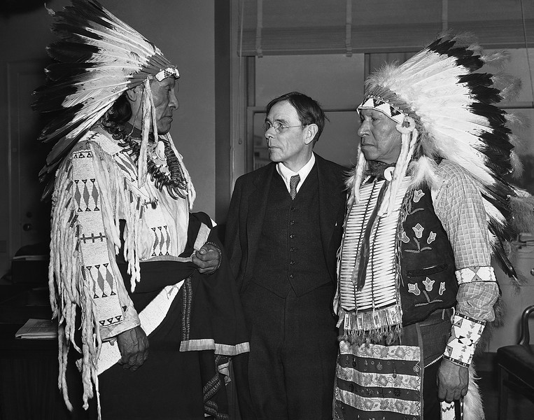 Description of  In full tribal regalia, Dewey Beard, left, and James Pipe-on-Head, survivors of the wounded knee creek massacre of 1890 in South Dakota, arrived in Washington on March 4, 1938, to testify in behalf of a bill to pay $1,000 to each of the survivors of the bloody fight in which 290 members of the Sioux Indian band were slain. They were greeted by John Collier, center, Commissioner of Indian Affairs. (AP Photo)