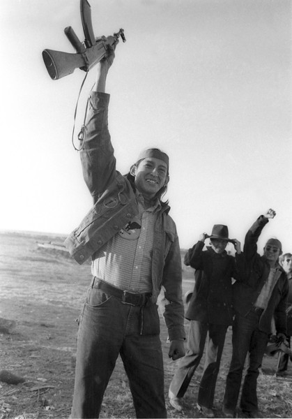 Description of  A member of the American Indian Movement (AIM) at Wounded Knee, S.D., March 8, 1973 raises his rifle and cheers after receiving news that federal authorities had extended the cease fire for further negotiations to end the standoff.  AIM was occupying the village that was the site of the 1890 Wounded Knee massacre. (AP Photo)