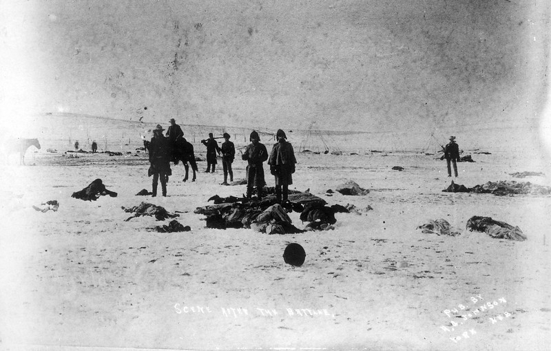 "Description of  ""Scene after the battle."" Jan. 1891. View southwest from center of council circle after the fight at Wounded Knee Creek, Pine Ridge Reservation, South Dakota, shows men holding moccasins and other souvenirs among the frozen bodies of Native American Lakota Sioux on the snow covered ground. (Denver Public Library; Western History Collection)"