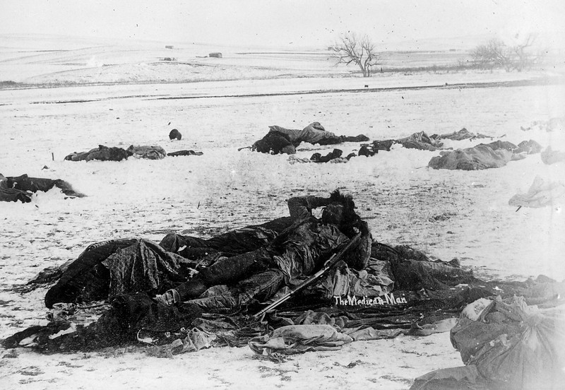 Description of  1891 January 3. The Medican [i.e. Medicine] Man. View of the slain frozen body of a Native American Lakota Sioux medicine man, Wounded Knee Creek, Pine Ridge Reservation, South Dakota. The body has clenched arms and is posed with a rifle. (Denver Public Library; Western History Collection)