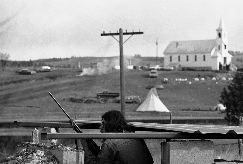 Description of  Indians on the Pine Ridge Indian Reservation at Wounded Knee, S.D. watch U.S. Marshals on the ridge beyond as both slides remained at a standoff on March 3, 1973 in Wounded Knee. (AP Photo)