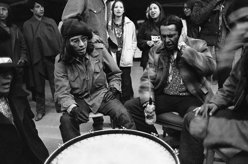 Description of  Russell Means, right, leader of the militant AIM group holding the village of Wounded Knee, S.D. on the Pine Ridge reservation, beats the drum at a meeting of the Indians, Friday, March 10, 1973. Man at left is not identified. (AP Photo)