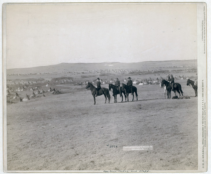 Description of  Title: General Miles and staff<br />Six military men on horseback on a hill overlooking a large encampment of tipis. 1891. <br />Repository: Library of Congress Prints and Photographs Division Washington, D.C. 20540
