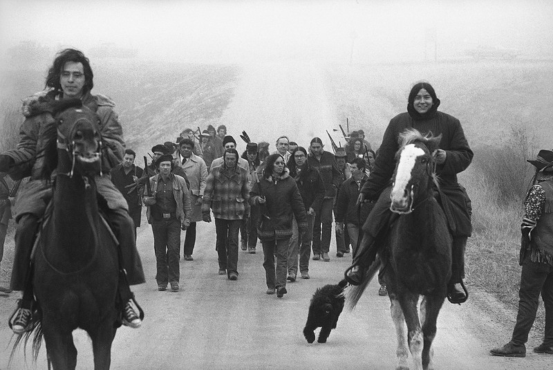Description of  Harlington Wood, Assistant U.S. Attorney General, third row center without hat, is escorted into the village of Wounded Knee by militant Indians of the AIM group, March 13, 1973. Second row, left, wearing mackinaw is Russell Means, one of the AIM leaders and Carter Camp, another leader walks beside Wood. Wood was sent to the reservation in an effort to find a solution to the problem. (AP Photo)