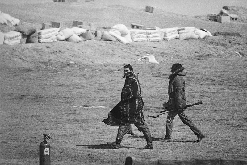 Description of  Blanketed against Wednesday's high wind, members of the American Indian Movement head toward bunkers at Wounded Knee, South Dakota, March 22, 1973. AIM and government negotiations remained deadlocked on Wednesday. (AP Photo/Fred Jewell)