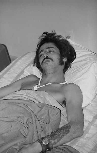 Description of  Rocky Madrid, a white medic, lies wounded in a make shift hospital in Wounded Knee, South Dakota on March 18, 1973, after being shot in the stomach during exchange of gunfire between AIM Native Americans and federal lawmen. (AP Photo/Jim Mone)