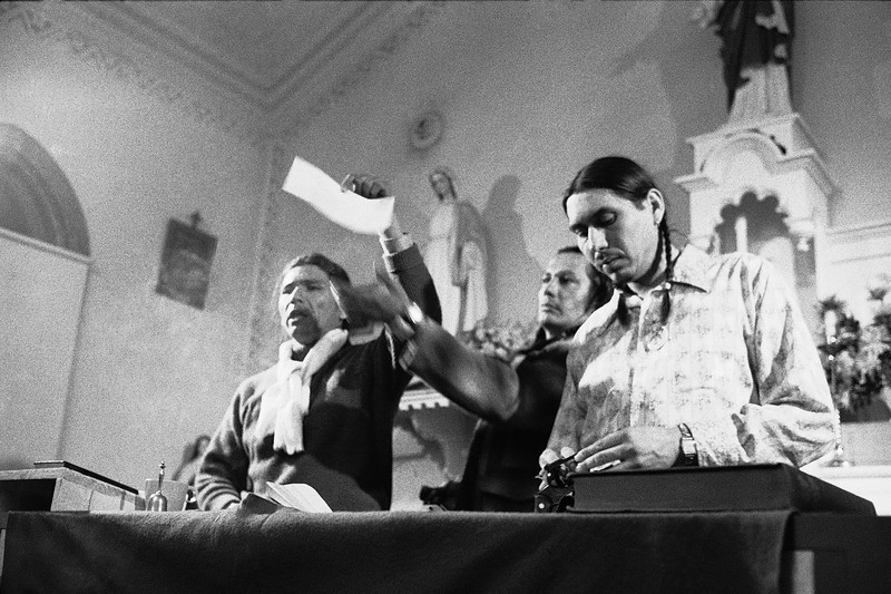 Description of  American Indian Movement leader Dennis Banks holds an envelope addressed to the Justice Department containing ashes of federal proposal for Indians to evacuate Wounded Knee, March 5, 1973 in Wounded Knee, SD.  AIM leaders burned the document. Russell Means, center, and Carter Camp look on. (AP Photo)