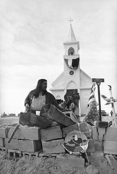 Description of  A unidentified Native American member of AIM sits in bunker with his rifle in front of church in Wounded Knee, South Dakota, March 2, 1973, that is still occupied by the Indians. Town of Wounded Knee is still in control of AIM. (AP Photo/Jim Mone)