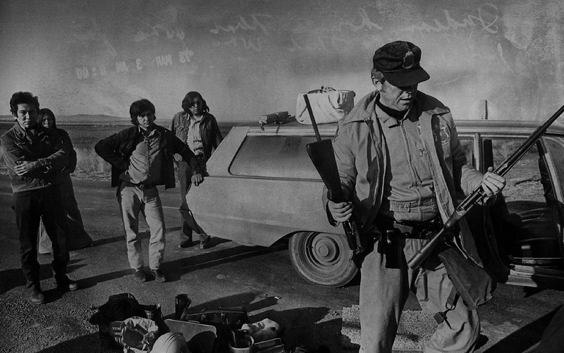 Description of  MAR 2 1973 - A Federal Marshal Confiscates Weapons from A car stopped at Road Block Seven Miles from Wounded Knee, S.D. Sen. George McGovern. D.S.D. reported that weapons were very much in evidence in the village and the damage that had been done was 'incredible.' (Dave Buresh/The Denver Post)