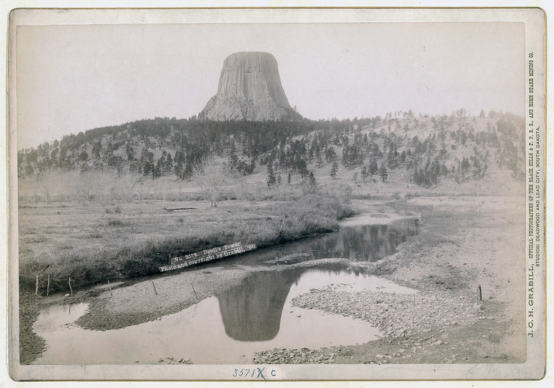 "Description of  Title: Devil's Tower. Distant view of Devils Tower and reflection of tower in stream in foreground. 1890. According to the National Park Service, over twenty tribes have potential cultural affiliation with the landmark. Among other names, The Lakota Sioux call Devils Tower ""Bear Lodge."" Repository: Library of Congress Prints and Photographs Division Washington, D.C. 20540"