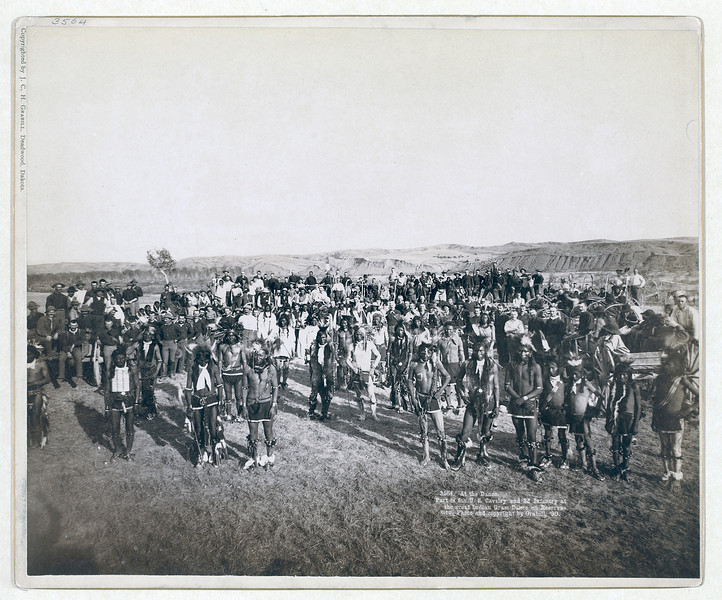 Description of  Title: At the Dance. Part of the 8th U.S. Cavalry and 3rd Infantry at the great Indian Grass Dance on Reservation<br />Group portrait of Big Foot's (Miniconjou) band and federal military men, in an open field, at a Grass Dance on the Cheyenne River, S.D.--on or near Cheyenne River Indian Reservation. 1890.<br />Repository: Library of Congress Prints and Photographs Division Washington, D.C. 20540