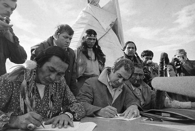 Description of  AIM leader Russell Means, left and assistant U.S. attorney general Kent Frizzell sign settlement of the Wounded Knee problem April 5, 1973 in South Dakota. Looking on left is Frizzells assistant Richard Helstern and AIM leader Dennis Banks. (AP Photo)