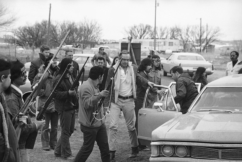 Description of  Harlington Wood, right, of the U.S. Attorney General's office, is escorted by armed AIM supporters from car to conference with AIM leaders in Wounded Knee, South Dakota, March 19, 1973, as efforts to end the occupation of Wounded Knee continue. (AP Photo)